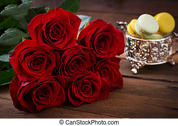 Bouquet of red roses on a dark wooden background.