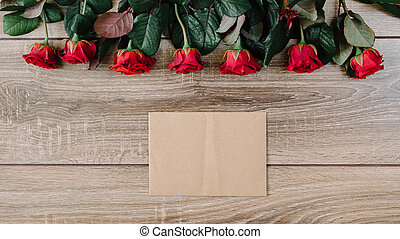 Bouquet of red roses on a wooden table with an envelope and a blank paper card for your text