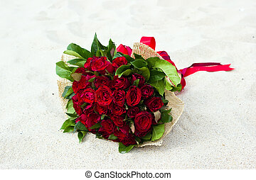 Bouquet of red roses on the beach