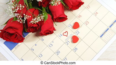 Bouquet of red roses on the calendar showing 14th February 4k