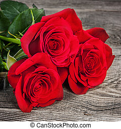 Bouquet of red roses on the old boards
