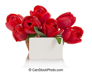 Bouquet of red tulips in a basket and card