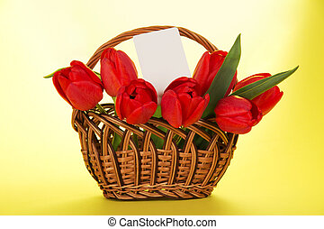 Bouquet of red tulips in basket and white card