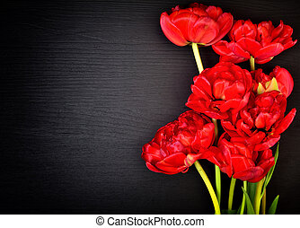 Bouquet of red tulips on a black wooden surface