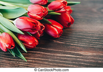 Bouquet of red tulips on a wooden background