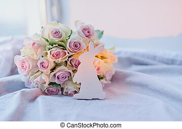 bouquet of roses and a wooden rabbit