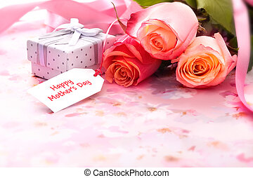 Bouquet of roses and gift box with a mothers day card