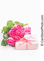 Bouquet of roses next to a gift with a  happy mothers day card