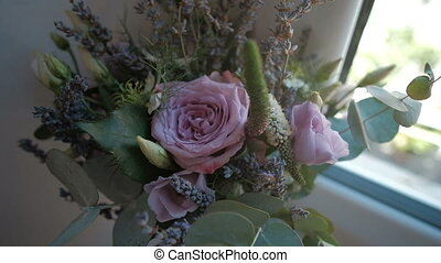 Bouquet of roses of different colors standing on windowsill...