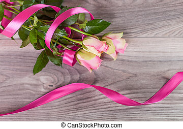 Bouquet of roses with pink ribbon on wood