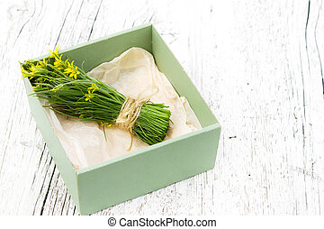 bouquet of small yellow flowers in a box on a wooden background blurred