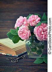 Bouquet of tea roses in glass vase on wooden background