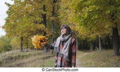 bouquet of the yellow leaves. Autumn girl walking in city...
