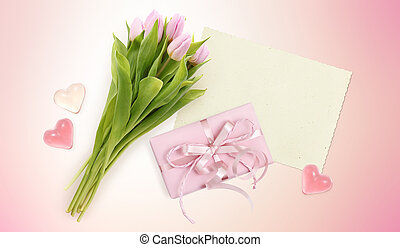 bouquet of tulips, card, hearts and box gift on pink background