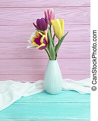 bouquet of tulips in a vase on a wooden background