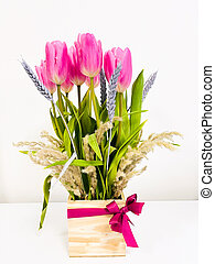 Bouquet of tulips in a wooden vase on white background.