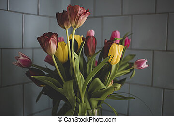 Bouquet of tulips on a background of blue tiled wall, in natural light from the window.