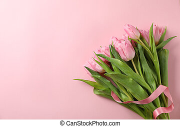 Bouquet of tulips on pink background, space for text