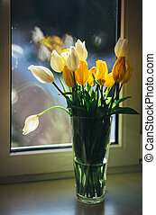 Bouquet of tulips standing at the window on a sunny day