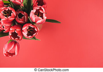 Bouquet of tulips with a note on a red background.