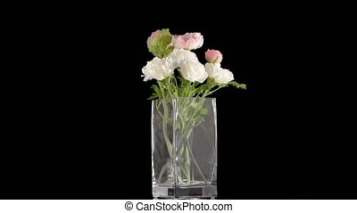 Bouquet of various artificial flowers in glass jar on white...