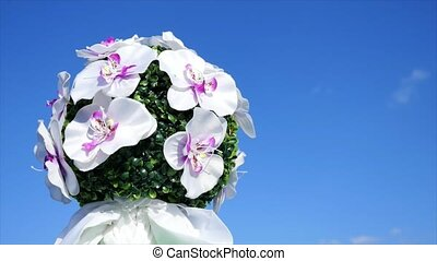 Bouquet of various flowers in the hand against the blue sky