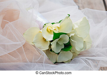 Bouquet of white calla flowers on a bride's dress.
