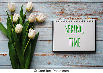 Bouquet of white flowers of tulips on the background of blue boards with a notebook with lettering Spring Time