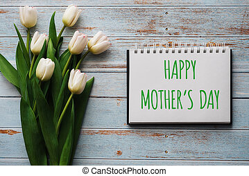 Bouquet of white flowers of tulips on the background of blue boards with a notebook with lettering Happy Mother's Day