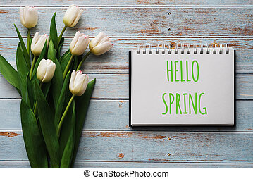 Bouquet of white flowers of tulips on the background of blue boards with a notebook with lettering Hello Spring