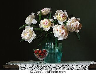 bouquet of white peonies and strawberries on a dark background.