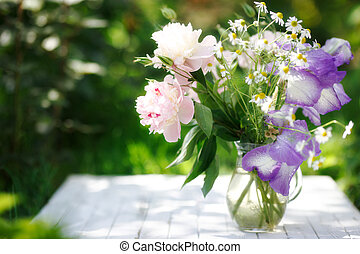 Bouquet of white peonies, chamomiles and iris flowers in glass vase. Summer background