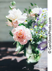 Bouquet of white peonies, chamomiles and iris flowers in glass vase. Summer background. Tinted photo
