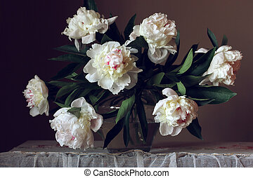 bouquet of white peonies in a glass vase on a dark background.