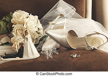 Bouquet of white roses, rings and satin wedding shoes on chair