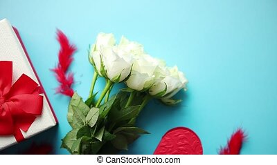 Bouquet of white roses with red bow on blue background....