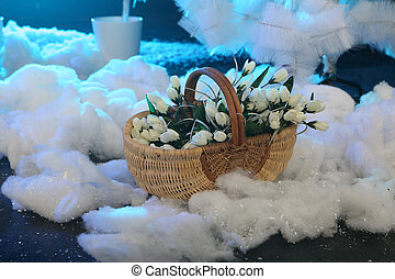 Bouquet of white tulips in a wattled basket on snow