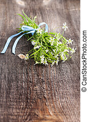 Bouquet of white wildflowers lying on a wooden table