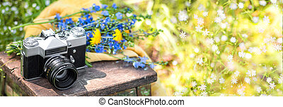 Bouquet of wild flowers and the retro film photo camera on a wooden chair in the summer garden.