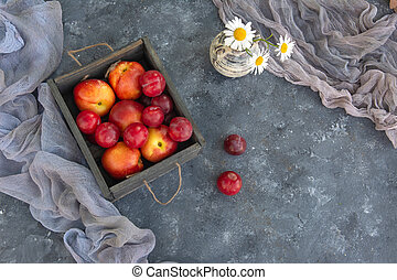 Bouquet of wild flowers chamomile with fruits of nectarines and plums in the wooden box