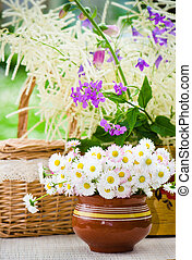 Bouquet of wild flowers in a pot at the table