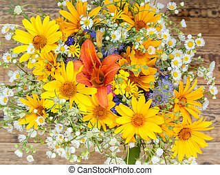 Bouquet of wildflowers on old wooden boards.