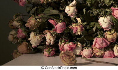 Bouquet of withered pink rose flowers. Dried roses on a table in dark room
