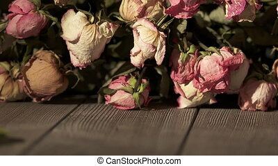 Bouquet of withered rose flowers on wooden table. Dried pink cream yellow roses