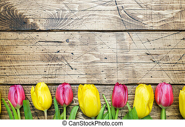 Bouquet of yellow and pink tulips on a wooden background.