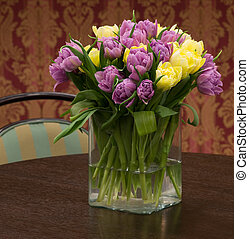 Bouquet of yellow and violet tulips in the glass vase