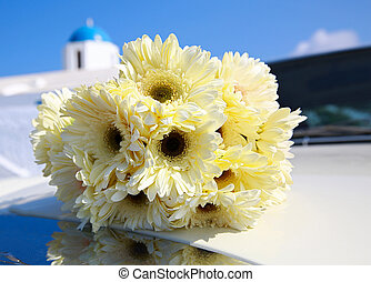 Bouquet of yellow chrysanthemums on the hood of the car. In...