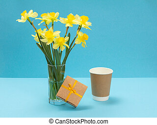 Bouquet of yellow daffodils in vase on a blue background.