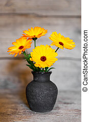 bouquet of yellow gerbera in a vase on wooden background