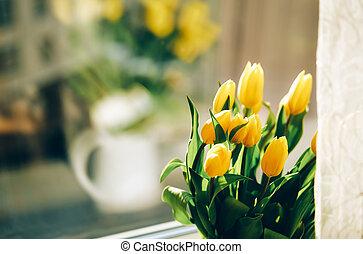 Bouquet of yellow tulip flowers on window sill